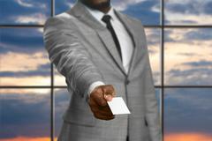Black businessman giving visit card. - stock photo