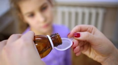 Doctor pours medicine syrup into measuring spoon and gives it girl. Stock Footage