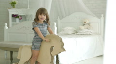 A little girl riding on wooden horse. Girl smiles. Stock Footage