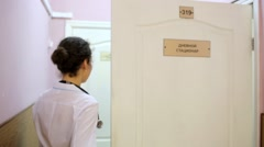 Female doctor in lab coat comes to room and closes door - stock footage