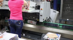 Female workers put a stacks of printed materials on tray of machine Stock Footage