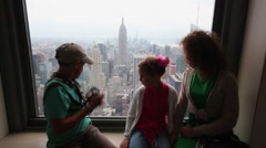 Family of three sit on windowsill in room at Observation Deck Top Stock Footage