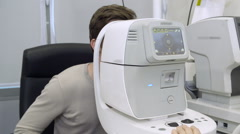 Doctor excaminating man's vision using machine Stock Footage