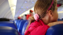 Closeup smiling little girl waves hand sitting in cabin of airplane. Stock Footage