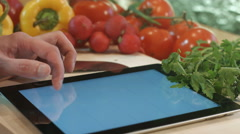 Man cooks looking writes prescriptions for a Tablet PC. salad cooking. Stock Footage