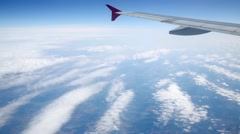 Wing and white cirrocumulus clouds through porthole Stock Footage