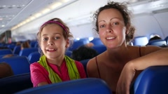 Mother and daughter talk sitting in cabin of flying airplane. Stock Footage