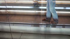 Male legs in jeans walking backwards by moving walkway Stock Footage