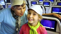 Boy and girl stand in cabin of airplane leaning on backseats. Stock Footage
