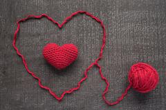 Crocheted red heart on a grunge board - stock photo