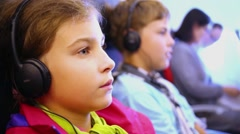 Girl in headphones listens to music sitting at cabin of airplane. Stock Footage