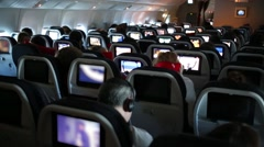 People at cabin of airplane. Backseats equipped with monitors. Stock Footage