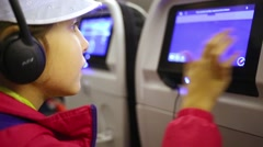 Little girl in headphones moves image on multimedia monitor Stock Footage