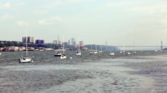 Large number of anchored sail boats against city and bridge. Stock Footage