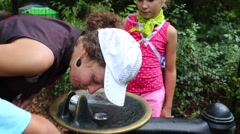 Woman and children drink water from drinking fountain in the park. Stock Footage