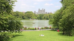 New York Central Park, people rest on grassy lawn and ride oar boats. Stock Footage