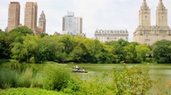 People ride in oar boats on pond at Central Park of New York City. Stock Footage