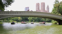 People rest in oar boats on pond and walk by Bow Bridge Stock Footage