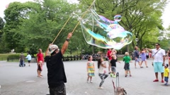 People look at man blows big soap bubbles entertaining visitors Stock Footage