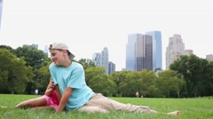 Girl and boy play sitting on grassy lawn in front of camera. Stock Footage