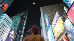 Man controls quadrocopter flying between highrise buildings Stock Footage