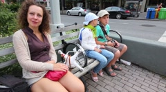 Mother and two children sit on bench at crossing Stock Footage