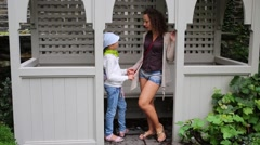 Mother and daughter talk standing at alcove in green summer park. Stock Footage