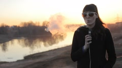 girl on a background of the river smokes an electronic cigarette - stock footage