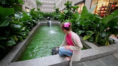 Little girl play with water at small basin with fountains Stock Footage