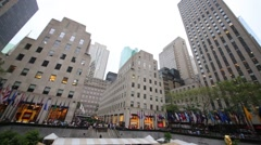 Rockefeller Plaza with buildings and flagpoles with flags Stock Footage