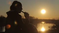 woman smokes an electronic cigarette at sunset - stock footage