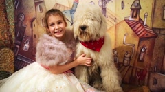 Little girl in evening dress and fur mantle sits with sagged dog Stock Footage