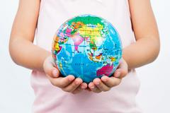 Little Kid Holding World Globe on Her Hands Stock Photos