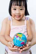 Asian Little Girl and Adult Holding a World Globe in Hands - stock photo