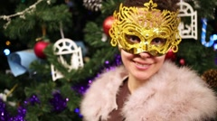 Woman in fur mantle and carnival mask against holiday fir tree. Stock Footage