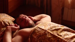Man wakes up and stretches in bed Stock Footage