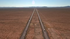 High aerial shot of vehicles on long straight highway in desert Stock Footage