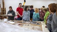 Guide and restorer talk with excursionists in restoration center Stock Footage