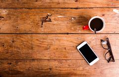 Smartphone, cup of coffee and eyeglasses on office desk - stock photo