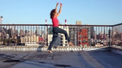 Young woman dances on roof against blue sky in the morning. Stock Footage