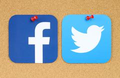 Facebook and Twitter icons printed on paper and pinned on cork bulletin board - stock photo