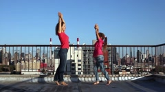 Young woman and girl jump at one place on roof against blue sky. Stock Footage
