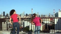 Young woman and girl do side bends on roof against blue sky. Stock Footage