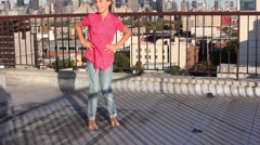 Little girl spins jumping at one place on roof against blue sky. Stock Footage