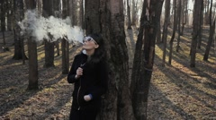 Young girl with glasses smokes an electronic cigarette in the park Stock Footage