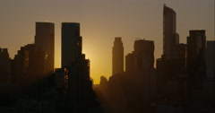 The sun peeks out from behind the Manhattan Skyline early morning. Stock Footage