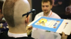 Man examines 3D glasses at Third International Exhibition MATE 2015 Stock Footage