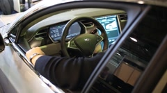 Man sits at passenger compartment of electric car Tesla Model S Stock Footage
