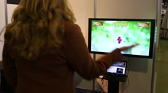 Visitor plays game on monitor that reacts to gestures without touching Stock Footage