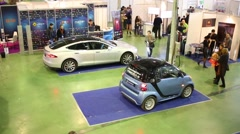 Visitors in room with Tesla Model S and Smart Fortwo Electric Drive Stock Footage